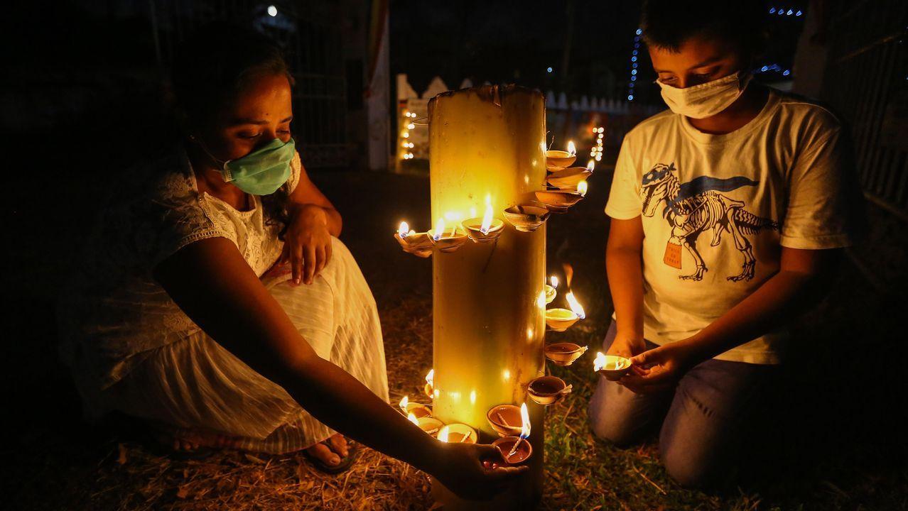 Los devotos budistas de Sri Lanka, con mascarillas, encienden lámparas de aceite durante las celebraciones religiosas del día de luna llena de Poson en un templo
