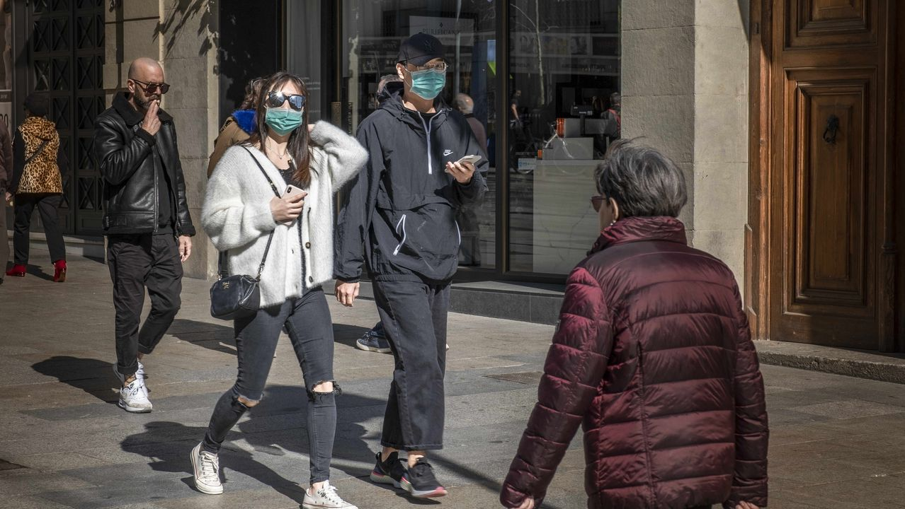 Una pareja pasea con mascarilla por el centro de Barcelona