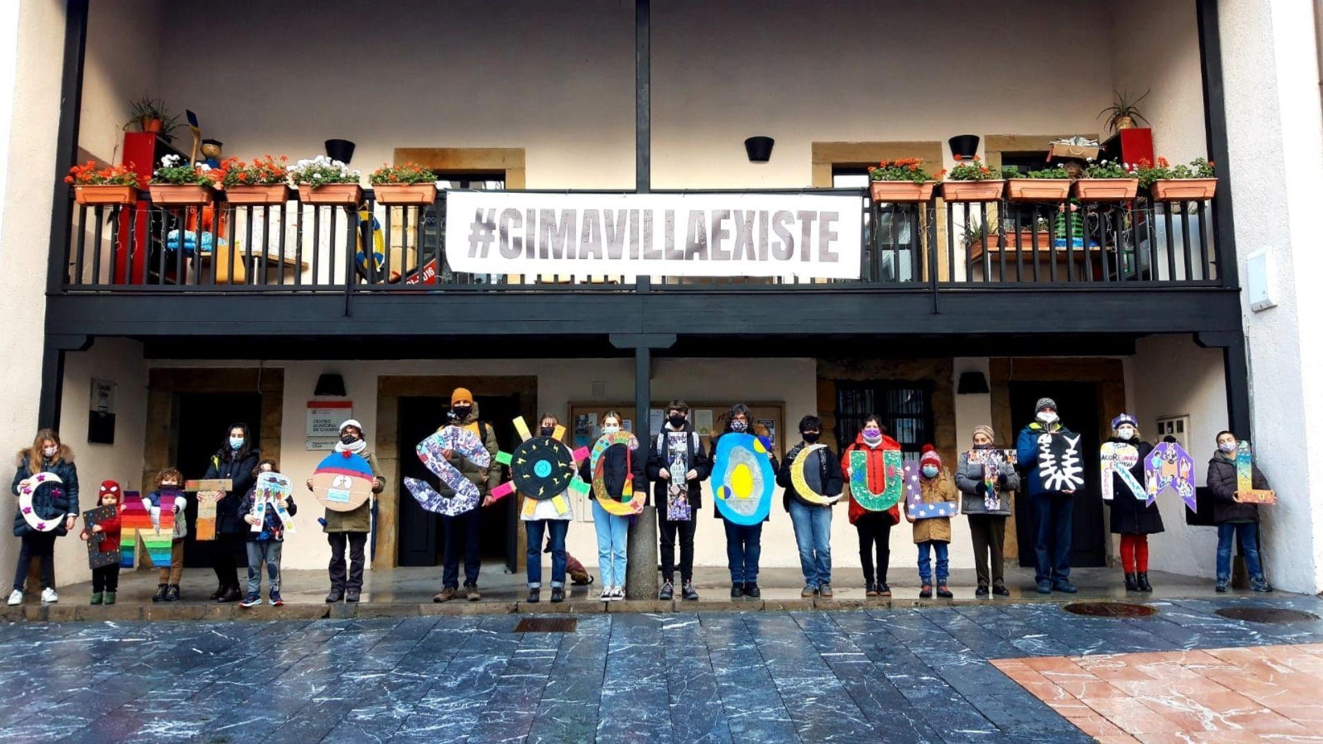 Los participantes en la iniciativa posan con las letras que conforman centro sociocultural delante de la Casa del Chino
