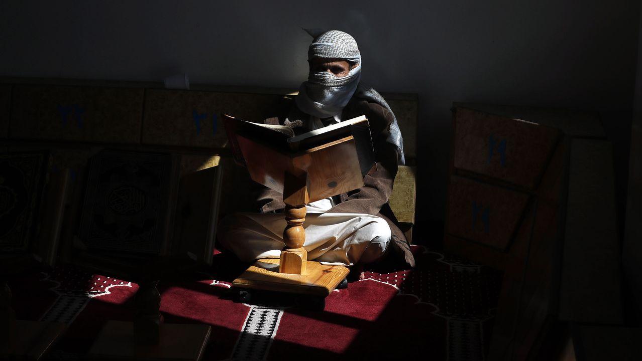 Un yemení lee el Corán portando una mascarilla en la capital del país, Saná
