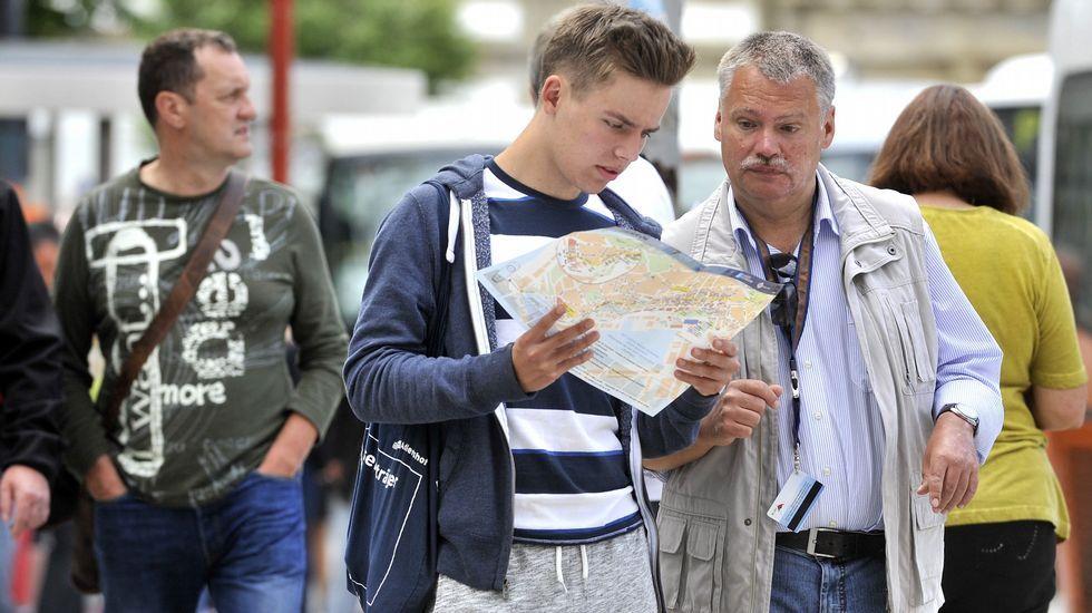 La «Méndez Núñez» zarpa de Ferrol para asumir el mando de la OTAN.Dos cruceristas alemanes consultan un mapa de Ferrol