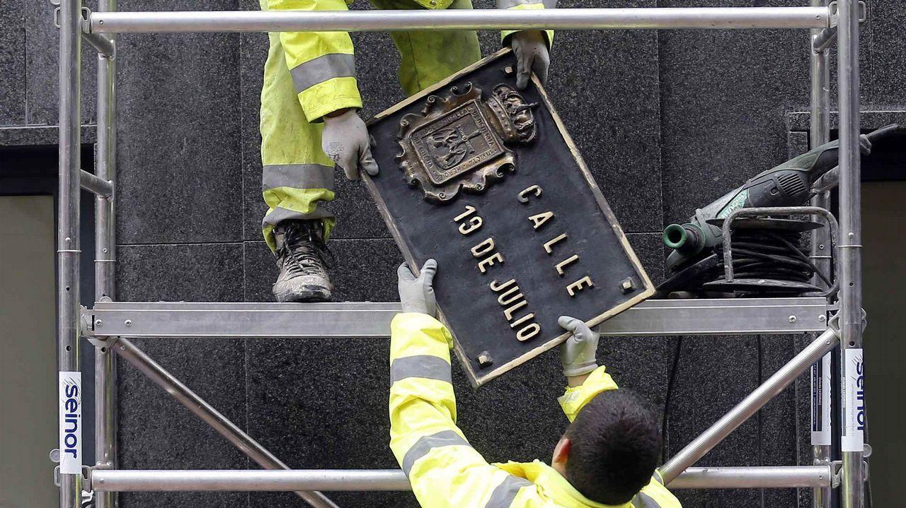 Dos operarios trabajan en la sustitución de la placa de la calle 19 de Julio, en el centro de Oviedo, en aplicación de la ley de Memoria Histórica por parte del Ayuntamiento de Oviedo