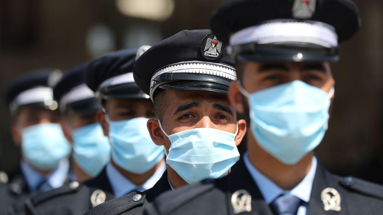 Los cadetes de la policía palestina, durante su acto de graduación, con mascarillas