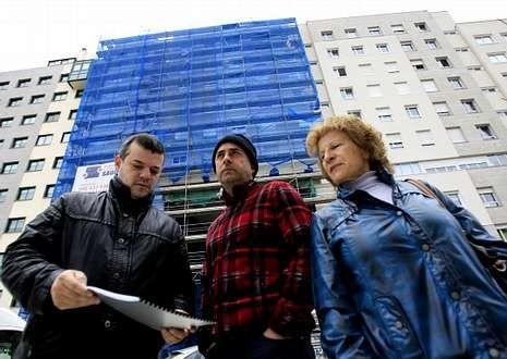 La presidenta de la comunidad junto con dos vecinos del edificio de la plaza de A Miñoca.