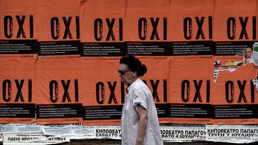 Jueves de colas y propaganda en las calles griegas.Una mujer custodiada por un policía mientras saca efectivo de un cajero automático en las calles de Atenas.