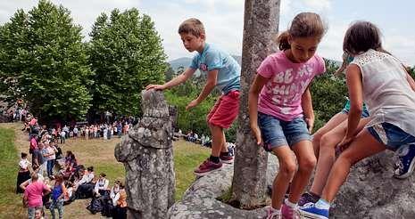 Unos niños juegan en las piedras del monte mientras los romeros asisten a la misa en los exteriores de la capilla, al fondo.