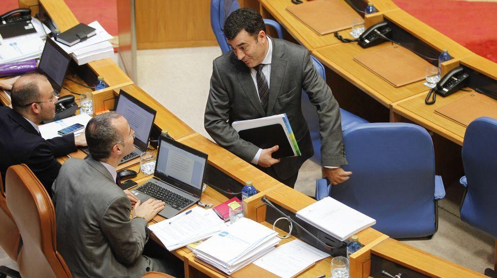 De conselleiro a exconselleiro. El nuevo conselleiro de Educación, Román Rodríguez (de pie), charla con su antecesor, Jesús Vázquez, durante la sesión de ayer en el Parlamento