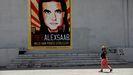 Una mujer paseando en Caracas ante un cartel que pide la libertad de Álex Saab.