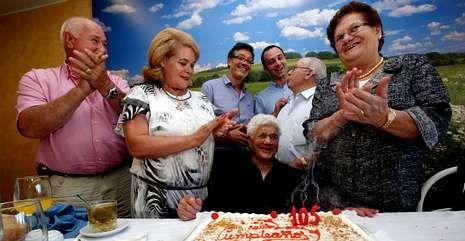 Balbina Blanco, en el centro, con algunos de sus parientes y el alcalde y un edil de Zas, soplando la segunda tarta de la jornada.