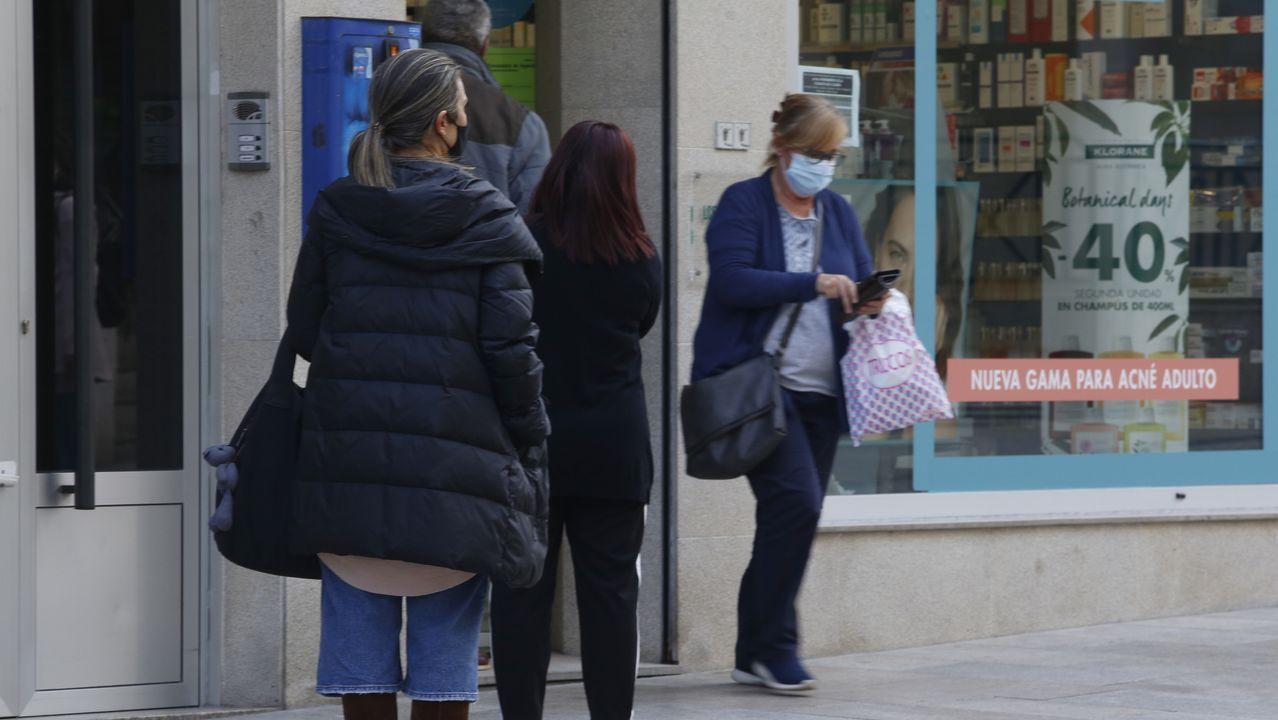 Vecinos de Arteixo hacen cola para entrar en un comercio de la calle peatonal