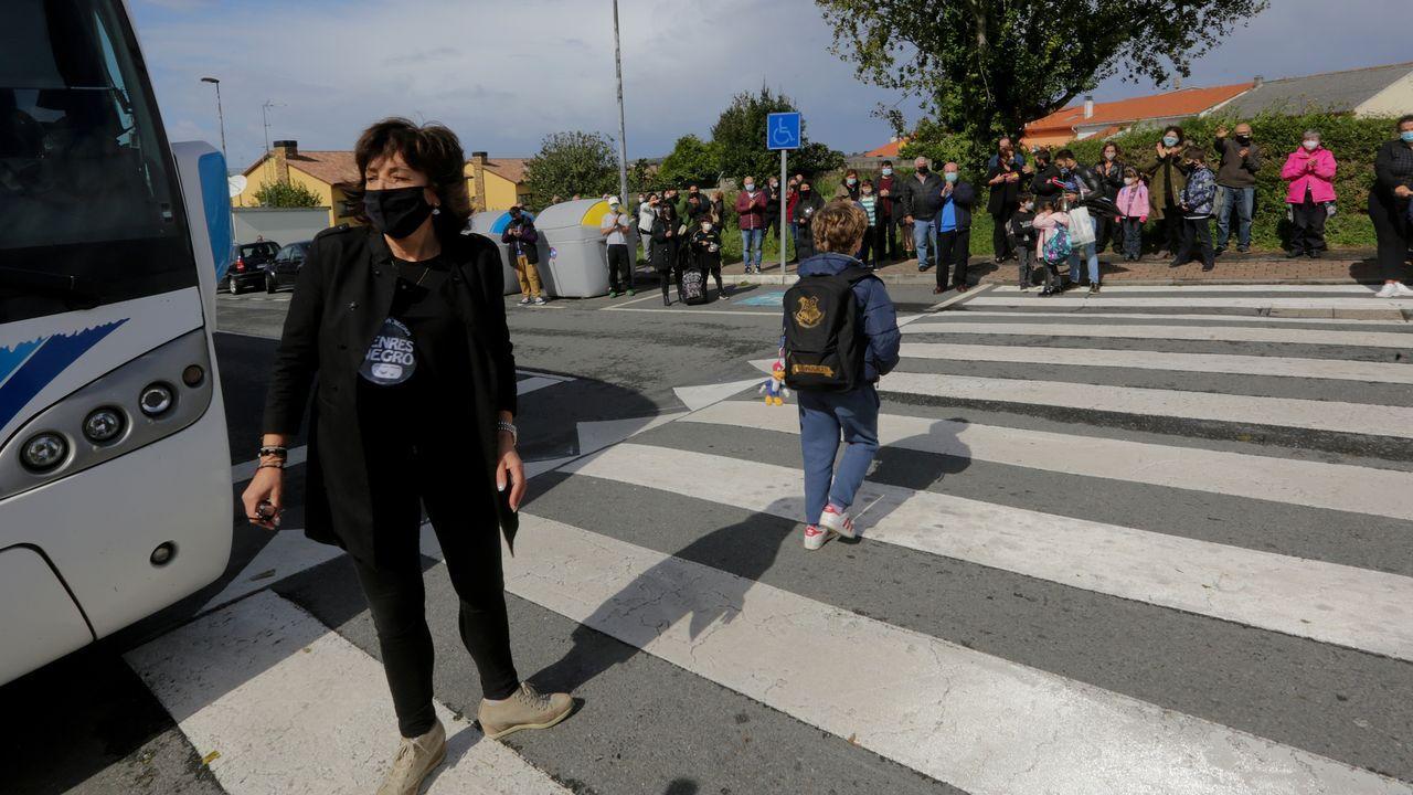 La directora, el viernes, a la salida del colegio de Mera, con un grupo de padres, al fondo, mostrándole su apoyo