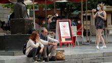 Una pareja de turistas fuma, con la mascarilla bajada, en el centro de Oviedo