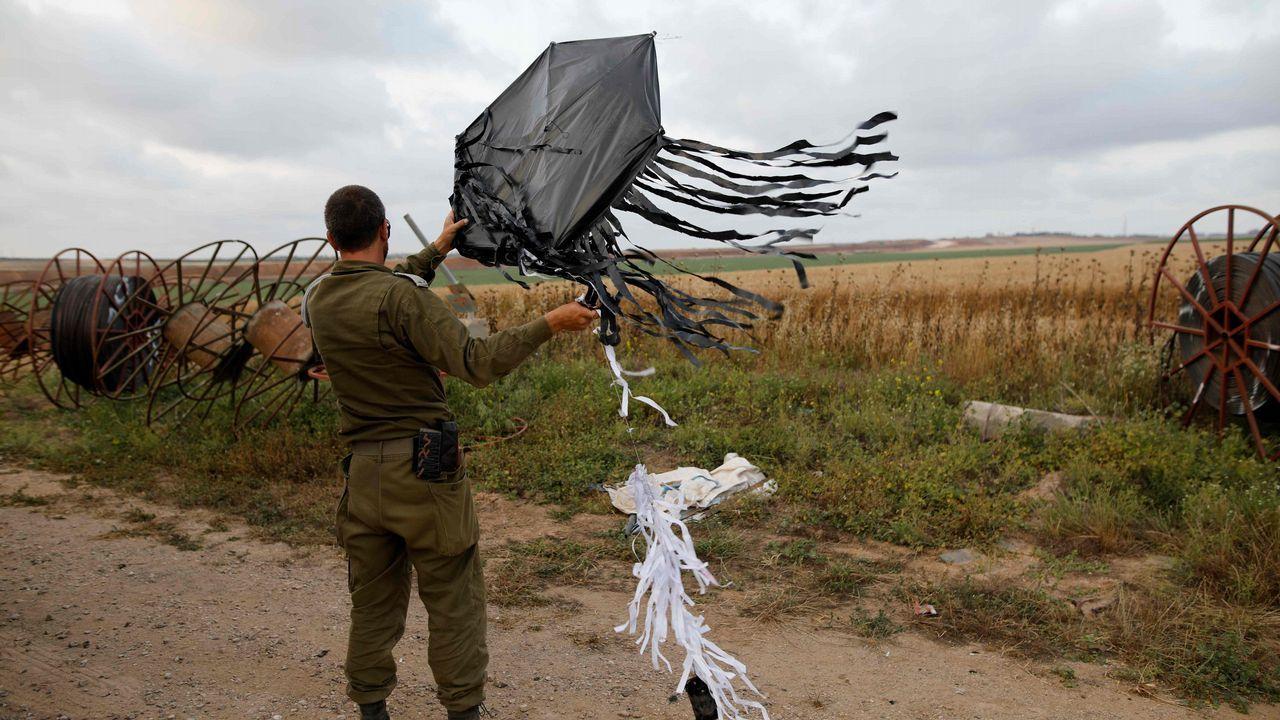Un soldado israeli sostiene una cometa que voló desde Gaza