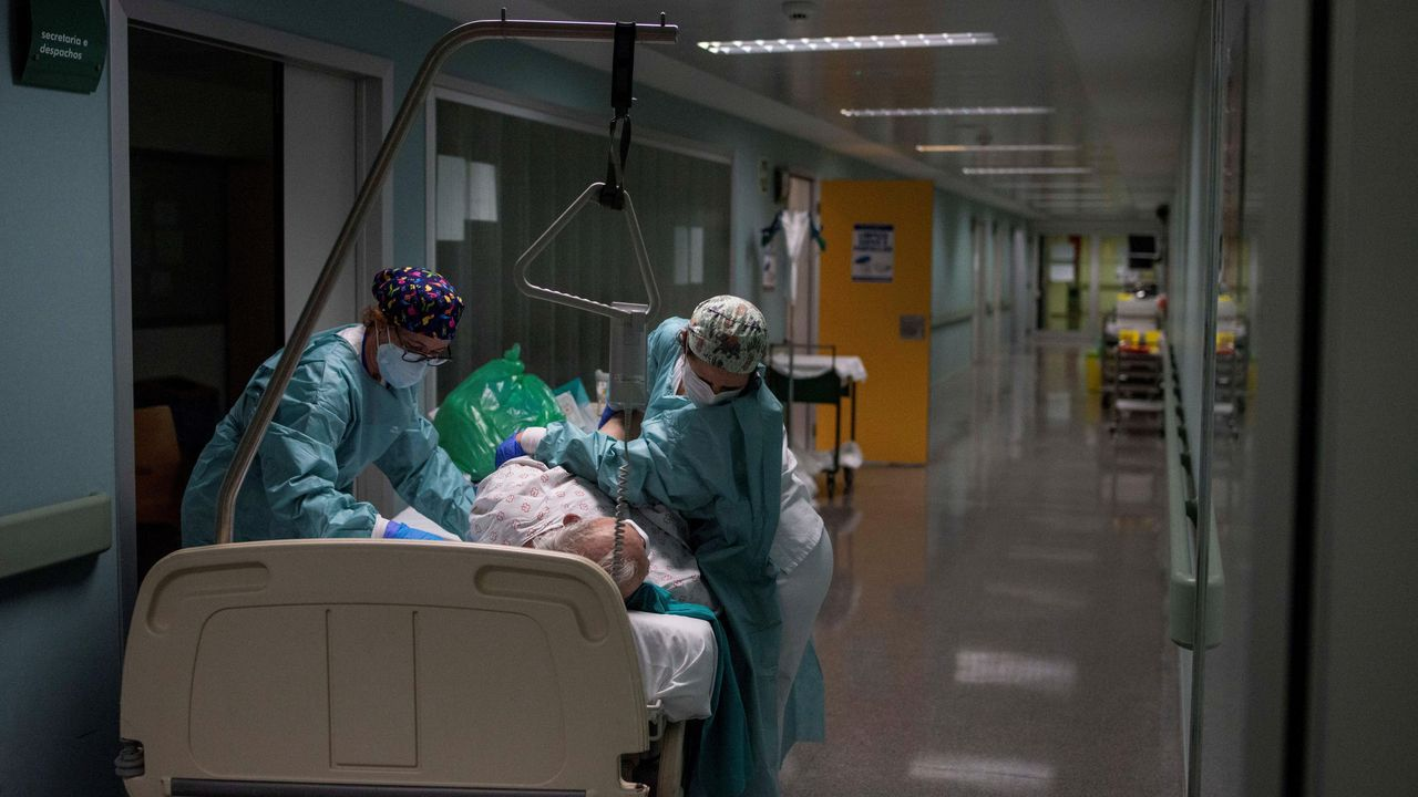 Sanitarios atienden a un paciente recuperado de coronavirus en el pasillo de la unidad de reanimación (REA) del Complejo Universitario de Ourense, este miércoles. Agotados pero al pie del cañón un día tras otro. Así están en críticos. No en vano, es la mejor definición del estado de ánimo de los profesionales sanitarios que lidian con los contagios de la covid-19, tanto desde Cuidados Intensivos (UCI) como en REA.