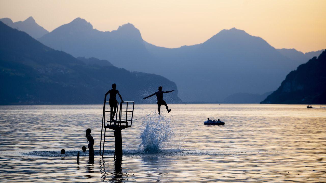 Varios jóvenes se dan un chapuzón en el lago Walensee en Walenstadt (Suiza)