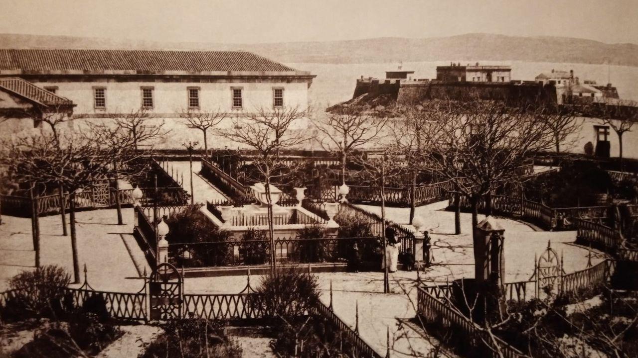 El jardín de San Carlos, en 1883, en la primera fotografía que se conoce, con el antiguo hospital y el castillo de San Antón al fondo. Los árboles son robinias. Aún no se habían plantado los olmos ni los setos que rodean los parterres actuales. El muro perimetral estaba recorrido por un banco.