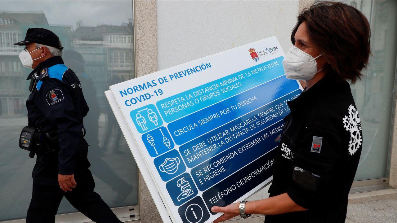 Una mujer coloca un cartel informativo en una calle de Viveiro