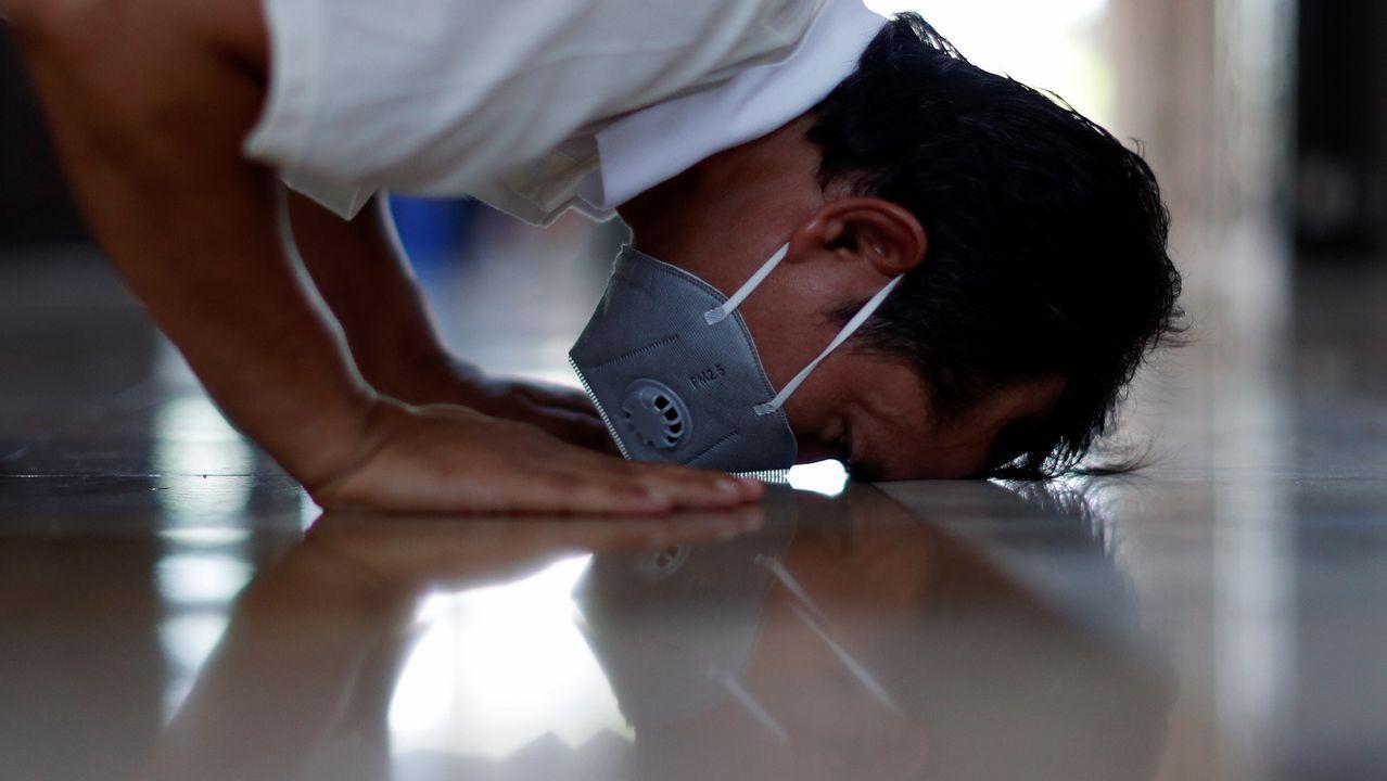 Un hombre con mascarilla ora durante el Ramadán en una mezquita de Bangkok