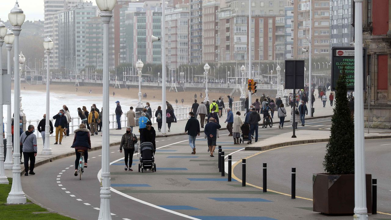 Varias personas caminan por el paseo de la playa de San Lorenzo de Gijón