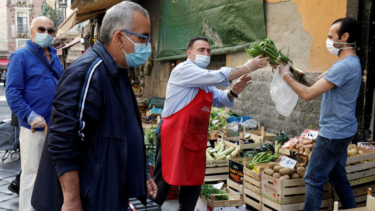 En Catania, Italia, los acuden a los mercados ataviados con mascarilla, igual que los vendedores