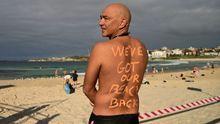 Un hombre posa en Bondi Beach, Australia, con el mensaje:  Tenemos nuestra playa de vuelta