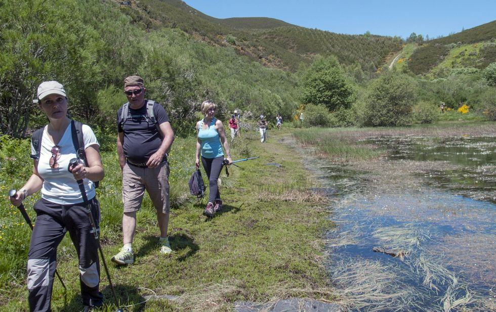 Un grupo de excursionistas para por la margen de la laguna glaciar de Lucenza.