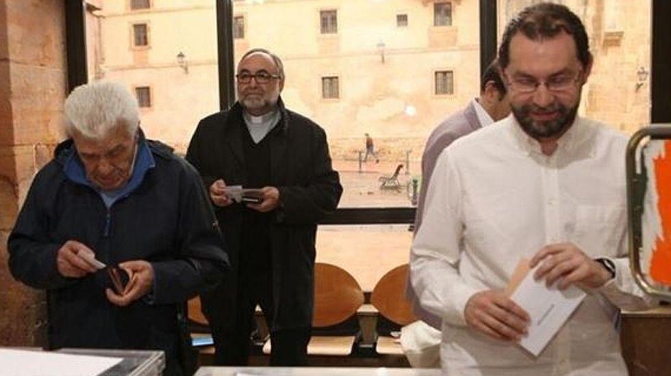 Emilio León, en primer plano, vota, mientras el Arzobispo de Oviedo espera su turno al fondo