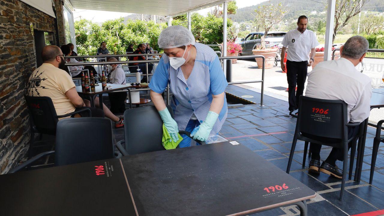 Limpiando la mesa de la terraza de un establecimiento de Viveiro