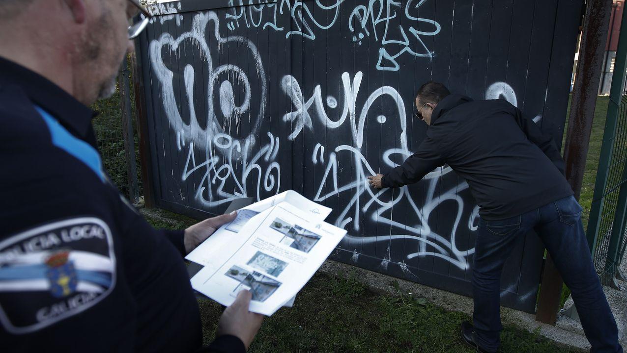 El temporal se ceba con Llanes.Antonio T. examina con un policía local un grafiti