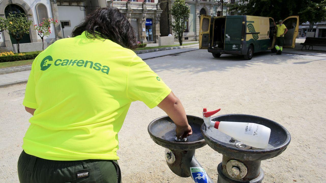 Una operaria procede al arreglo de una de las fuentes de la Praza Maior