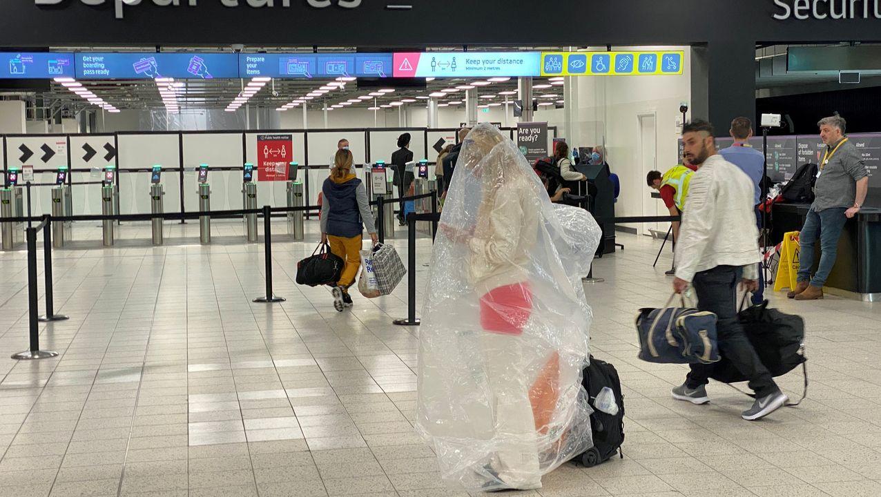 Un pasajero del aeropuerto londinense de Luton, envuelto en un plástico a modo de protección contra el covid