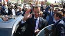 Bachar al Asad saluda a sus seguidores antes de abandonar el colegio electoral en el que votó, en las afueras de Damasco
