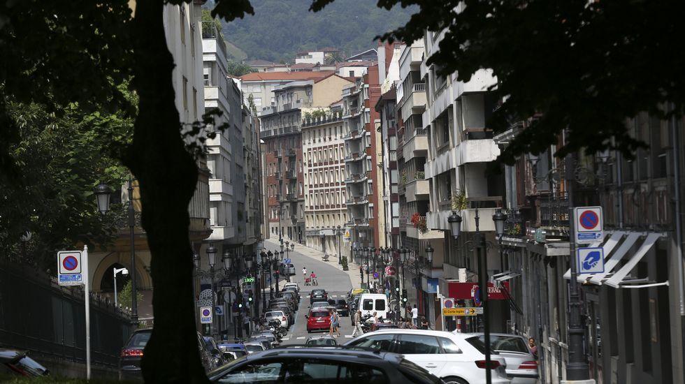 Un grupo de pasajeros consulta los vuelos en el Aeropuerto de Asturias.Edificios en la calle Marqués de Pidal, en Oviedo