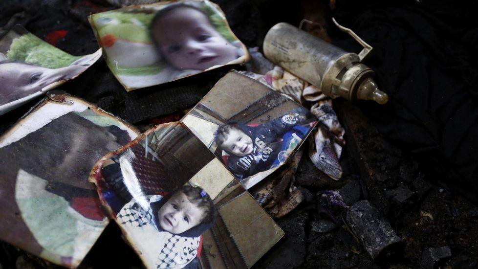 Batalla campal en Cisjordania.Un biberón descansa junto a las fotografías del bebé palestino de 18 meses, Ali Dawabsha.