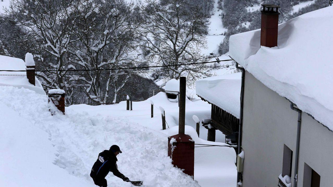 Carretera abierta alrededor de la nieve en Somiedo.Vecinos de Pajares (Asturias) retiran nieve del tejado de su casa de 300 años, una de las más antiguas del pueblo.