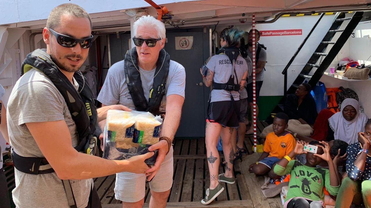 El actor Richard Gere (segundo por la izquierda) estuvo este viernes a bordo del Open Arms colaborando en el reparto de alimentos