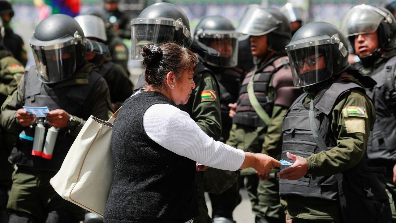 Una mujer entrega propaganda a las fuerzas de seguridad desplegadas en La Paz