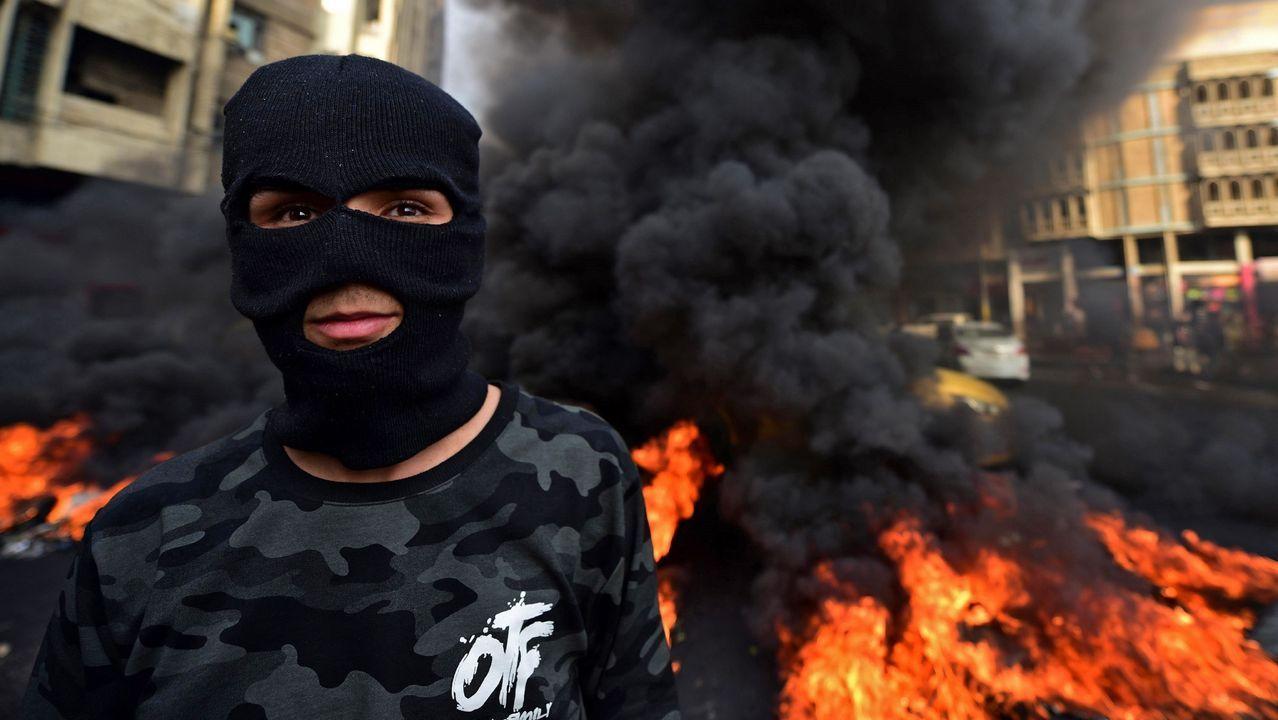 Un manifestante participa en la quema de neumáticos durante una protesta en la plaza Wathba de Bagdad