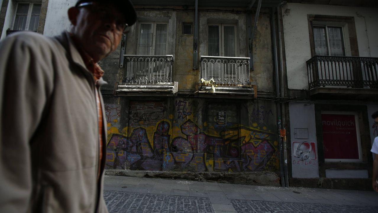 Así son los pisos que Cualedro alquila por 50 euros al mes.Un vecino pasa frente a varios edificios de la calle San Andrés