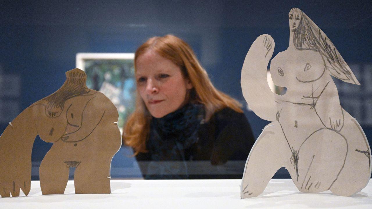 Una visitante observa dos desnudos femeninos realizados por Picasso en cartón dibujado