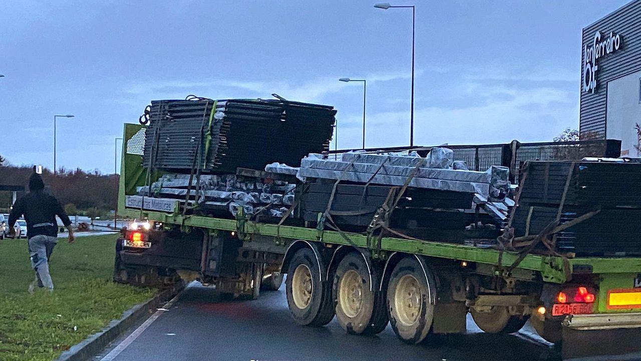 Un camión subido sobre el césped de la mediana para salir de una nave cargado