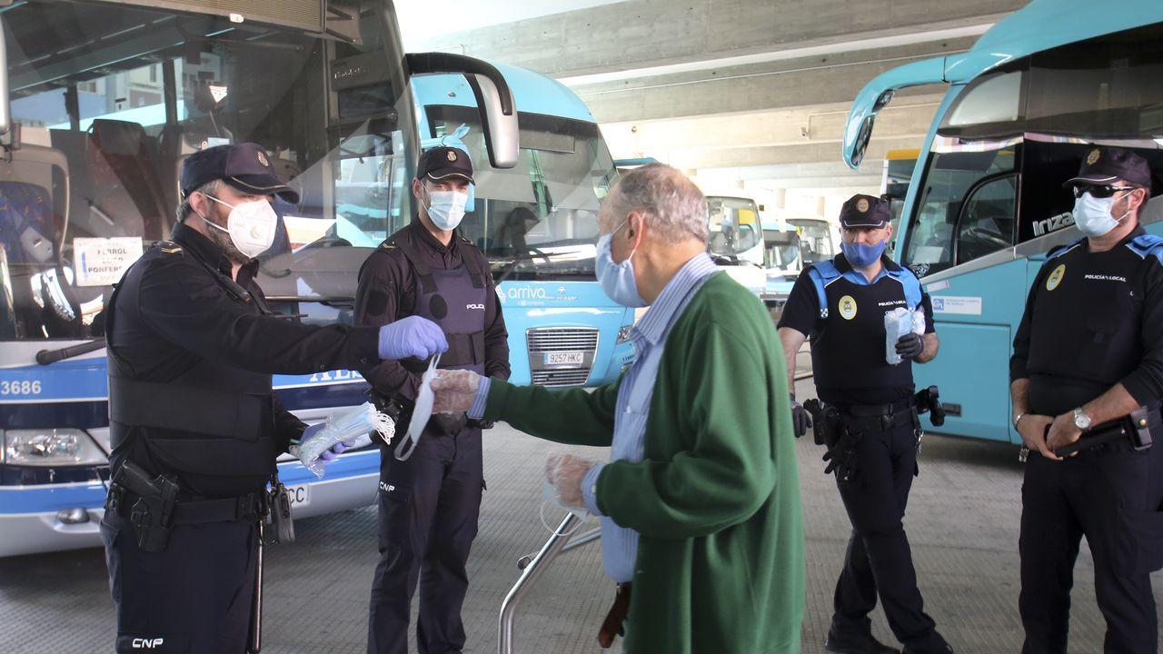 Agentes de la policía repartiendo mascarillas en la estación de autobuses de Ferrol