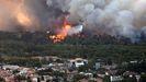 Un helicóptero antiincendios sobre vuela las llamas en el área de Varibombi, en las afueras de Atenas