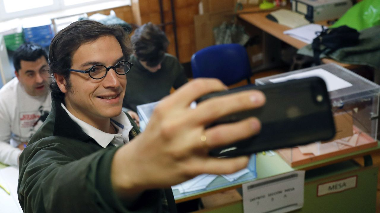 El candidato de Vox al Congreso por Asturias, José María Figaredo, se hace un selfi en la mesa electoral del colegio Pablo Miaja de Oviedo, en la que votó a primera hora de la mañana