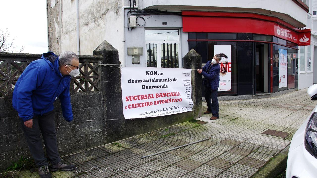 Dos hombres colgando una pancarta contra el cierre de la sucursal bancaria