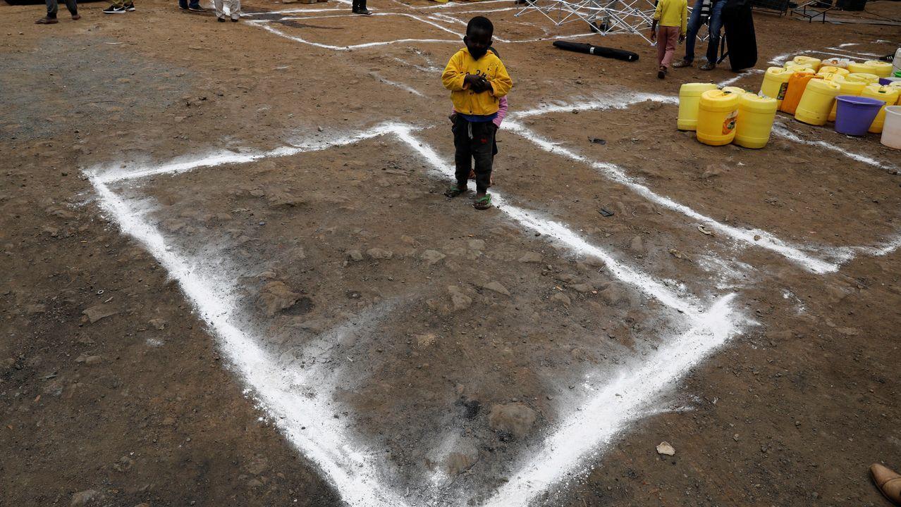 En Nairobi han dibujado rectángulos sobre la tierra para marcar la distancia social en un reparto de agua