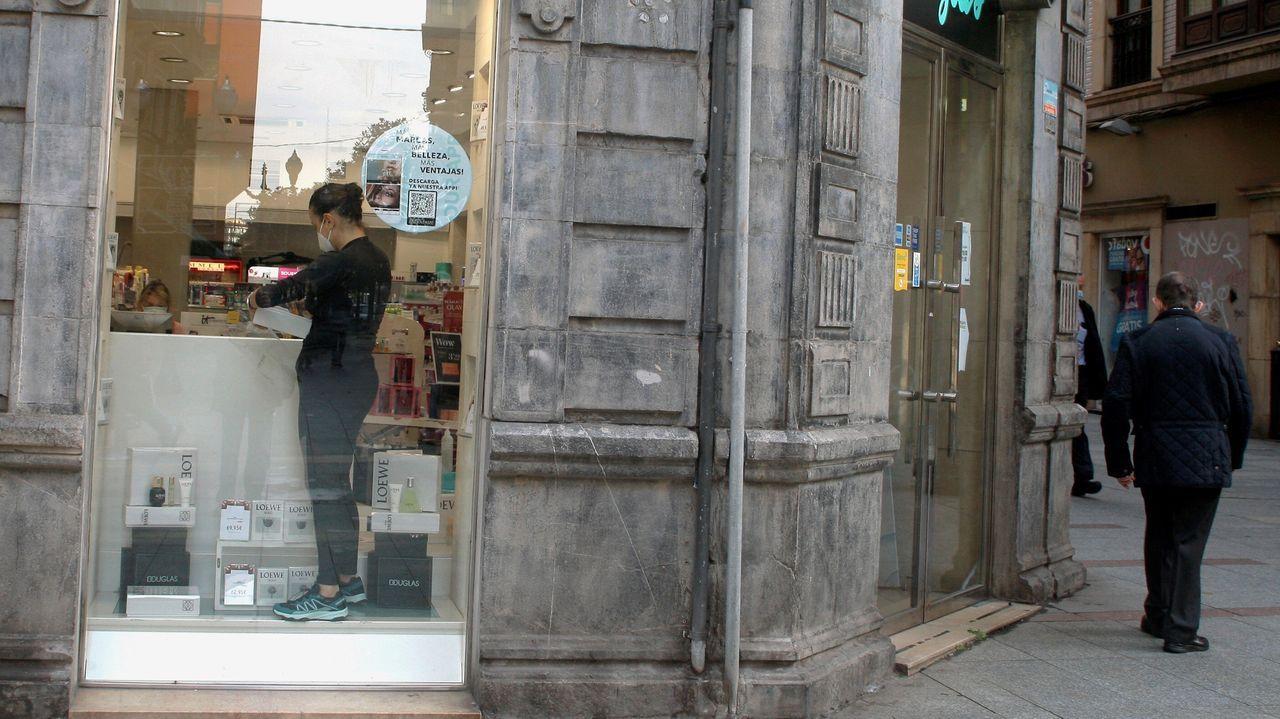 La empleada de un comercio minorista de Gijón prepara el local para abrir mañana al público