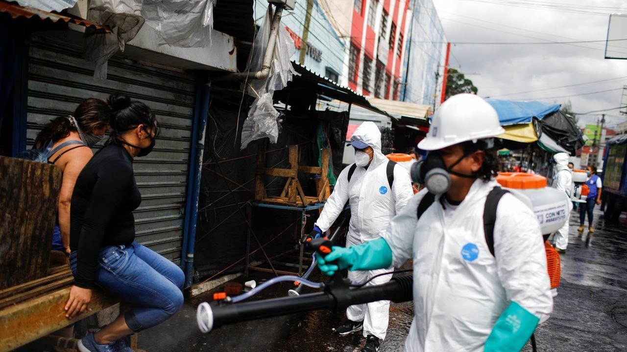 Trabajadores municipales desinfectan los puestos callejeros para comenzar a atender a los clientes a medida que la economía se reabre mientras continúa el brote de la enfermedad por coronavirus, en el centro de San Salvador, El Salvador