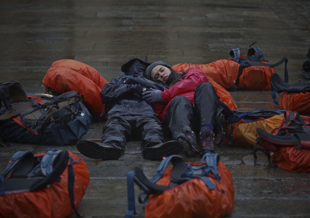 Peregrinos portugueses a su llegada al Obradoiro descansan sobre el suelo mojado