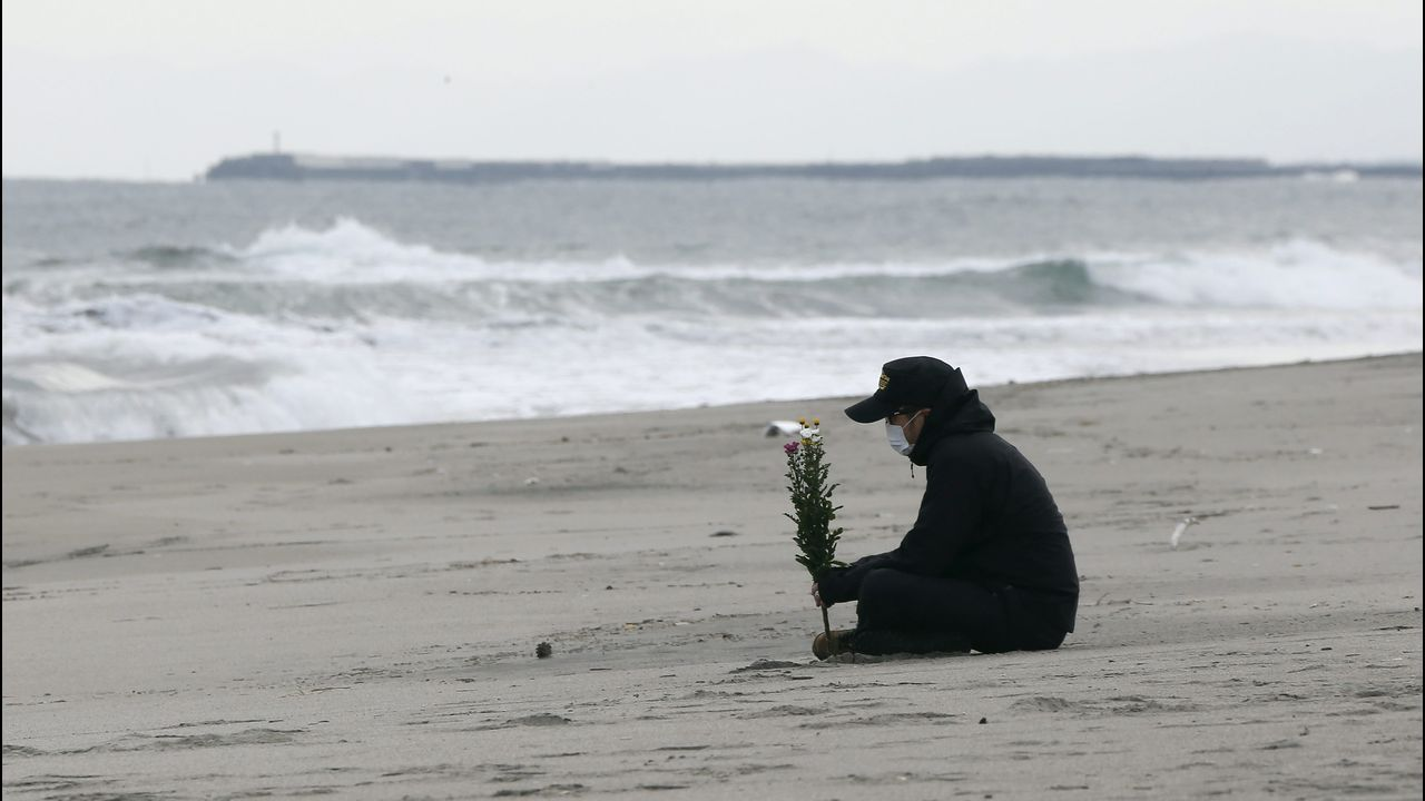 Regresan los temblores de Merkel durante un acto oficial.Un hombre sostiene un ramo de flores frente al mar en el aniversario del terremoto y posterior tsunami en Sendai, en el 2011